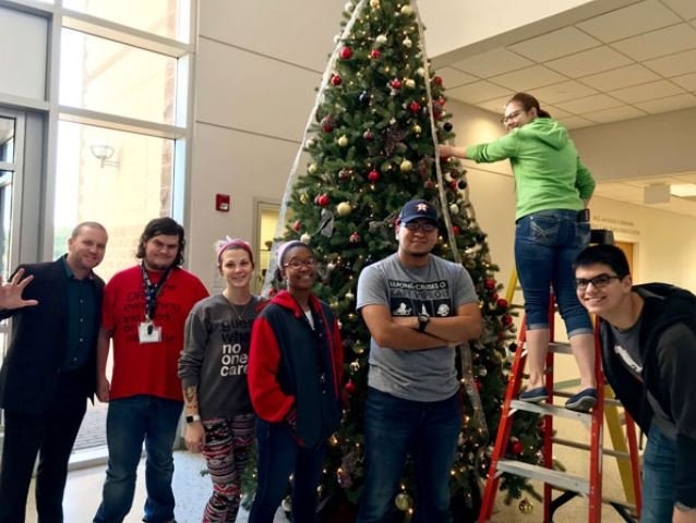 Michael Wilkinson, left, director of UHV Student Life & Services, helps decorate the UHV Giving Tree on Monday with freshman seminar students Dennis Barbee, Caralyn Podsim, Darinae Dixon, Luis Cigarro, Elizabeth Matula and Matthew Salinas. The Giving Tree